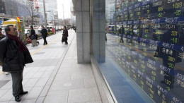 A pedestrian looks at an electronic stock board outside a securities firm in Tokyo. Photographer: Tomohiro Ohsumi