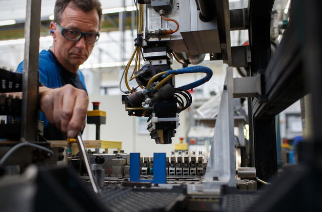 An employee works on the halogen light production line at the Royal Philips NV automotive lighting factory in Aachen, Germany