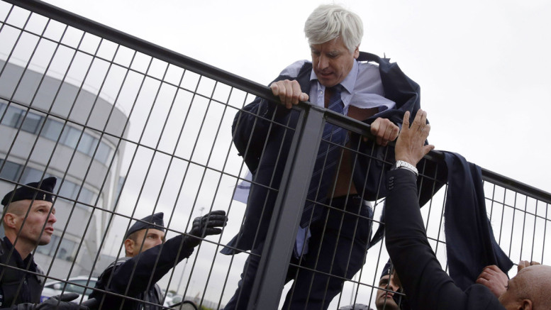 Director of Air France in Orly Pierre Plissonnier tries to cross a fence, helped by security and police officers