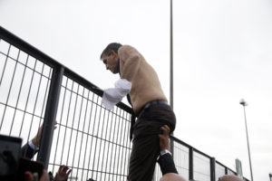 Air France human resources chief Xavier Broseta scales a fence away from protesters in Roissy-en-France, today. Photographer: Kenzo Tribouillard/AFP