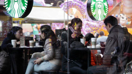 Customers sit inside a Starbucks Corp. outlet in Shanghai.Photographer: Tomohiro Ohsumi/Bloomberg