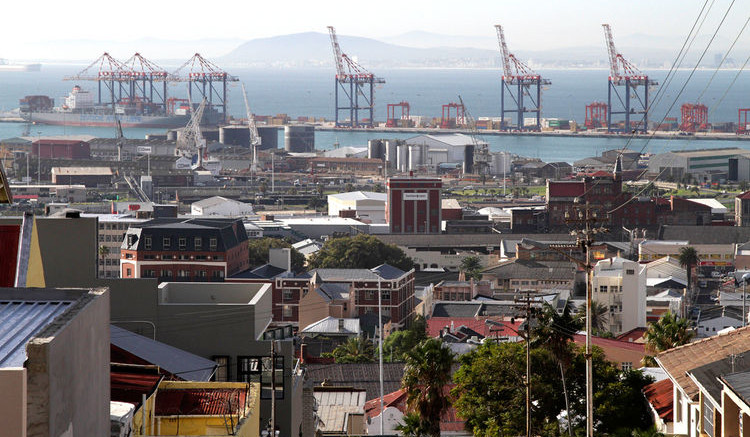 The residential district of Woodstock overlooks cranes on the harbourside in the commercial port area of Cape Town, South Africa. Photograph by Nadine Hutton