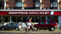 A bicyclist rides in front of a Shoppers Drug Mart Corp. store in Toronto, Ontario. Photographer: Brent Lewin