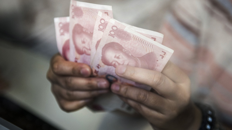 An employee at a currency exchange store counts Chinese one-hundred yuan banknotes in Hong Kong, China. Photographer: Xaume Olleros