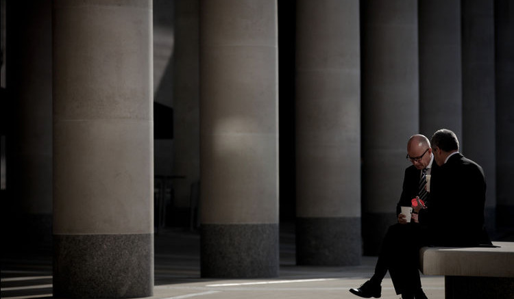 Businessmen sit outside the London Stock Exchange Group Plc headquarters in London. Photographer: Jason Alden