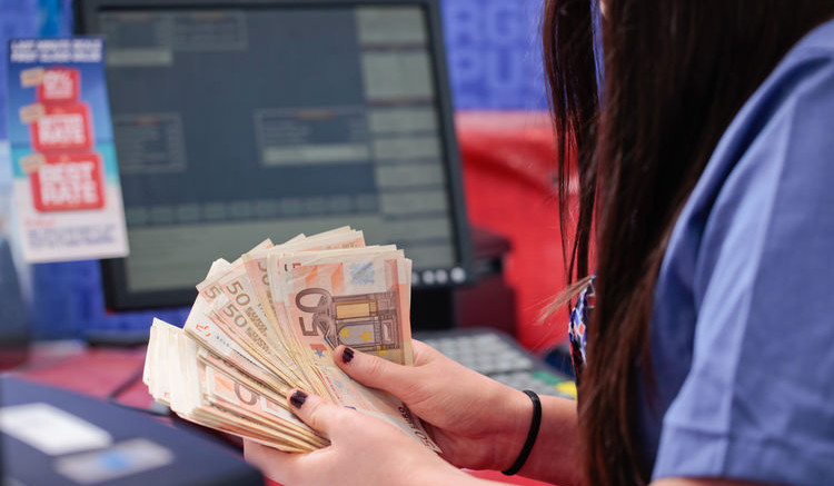 An employee holds a stack of fifty euro notes at a Travelex store at City airport in London.