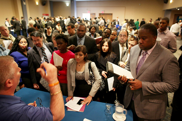 Job seekers line-up to give their resumes to an employment agency representivie at a job fair at a Holiday Inn in New York City. Photograph by Spencer Platt/Getty Images