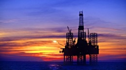 B7NRRE Silhouette of oil platform in sea against moody sky at sunset