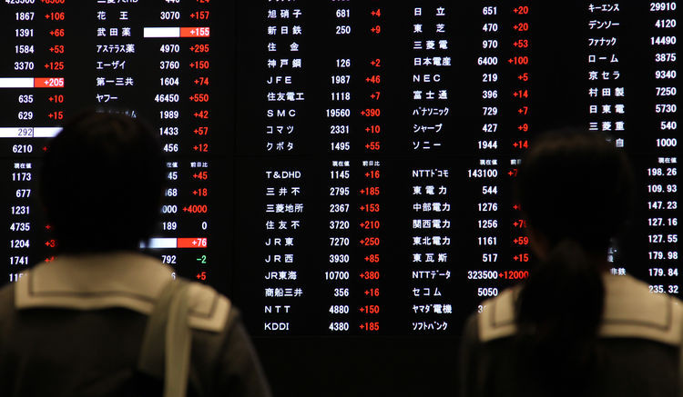 Visitors look at an electronic board displaying stock figures at the Tokyo Stock Exchange in Tokyo. Photographer: Junko Kimura