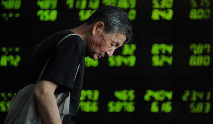 An investor observes electronic board at a stock exchange hall on July 7, 2015 in Shenyang, Liaoning Province of China. Photographer: ChinaFotoPress via Getty Images