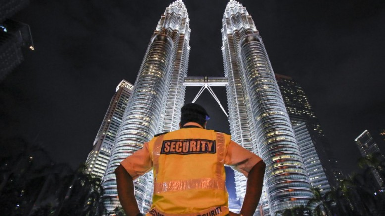 A security guard stands guard in front of Malaysia's iconic building, the Petronas Twin Towers