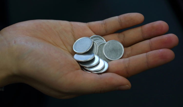 Aluminum coins to be minted into 1 Japanese yen coins are held for a photograph at the Akao Aluminum Co. plant in Tokyo. Tomohiro Ohsumi