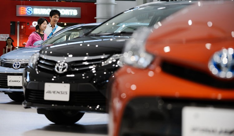 Visitors look at a Toyota Motor Corp. Camry sedan on display at the company's Mega Web showroom in Tokyo. Photographer: Akio Kon