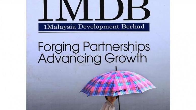 A woman walks past a 1Malaysia Development Berhad (1MDB) billboard in Kuala Lumpur. Photo: Reuters