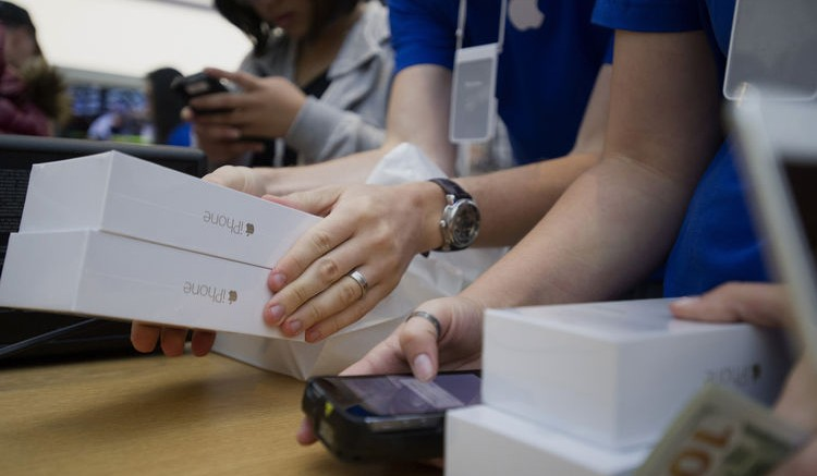 Boxes of iPhone 6 smartphones sit stacked on a table as customers make a purchase during the sales launch at the Apple Inc. store in Palo Alto, California. Bloomberg