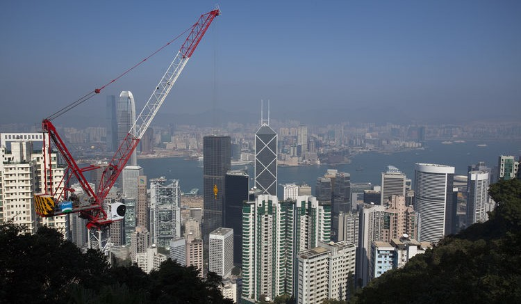 A construction crane operates as residential and commercial buildings rise above the business district of Central in Hong Kong, China, on Thursday, Dec. 29, 2011. Photographer: Jerome Favre