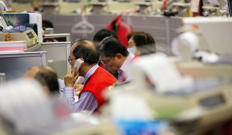 Traders work on the trading floor of the Hong Kong Stock Exchange in Hong Kong. Photographer: Lam Yik Fei