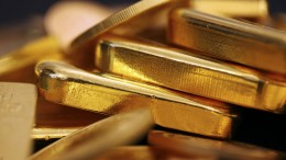 Gold bars and coins are seen in this arranged photograph at a bullion dealers in London. Photographer: Chris Ratcliffe