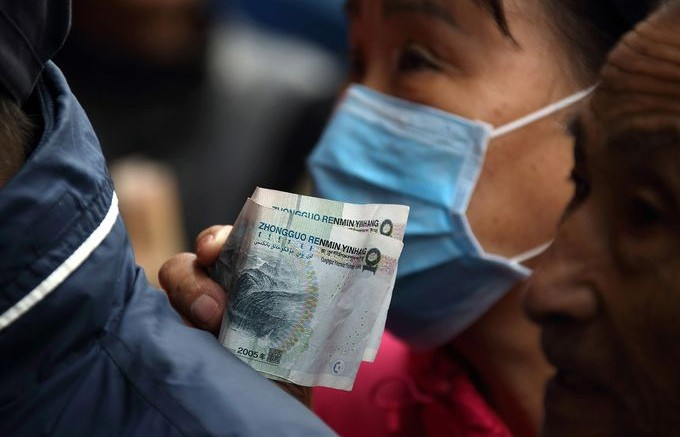 Customers hold Chinese yuan banknotes as they purchase Beijing ducks at a store in Beijing, China.