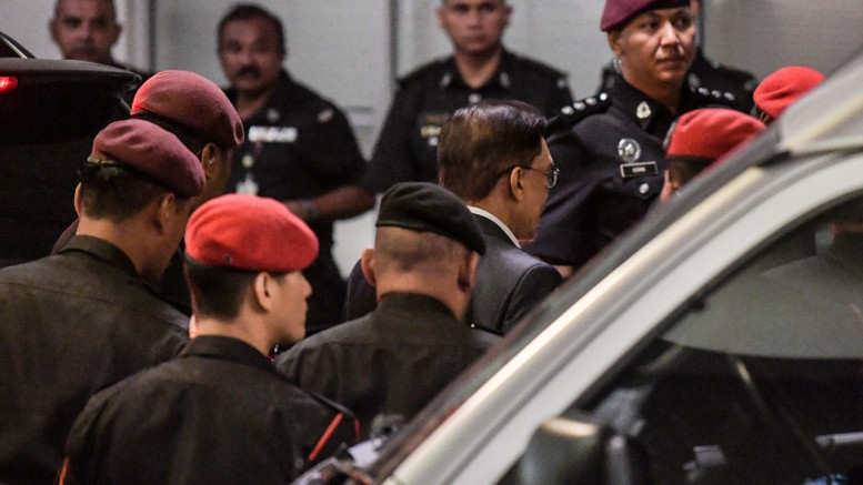Jailed Malaysian politician Anwar Ibrahim (2nd R) is escorted by prison security during his arrival at the federal court in Putrajaya on December 14, 2016.