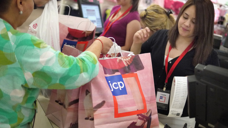NORTH RIVERSIDE, IL - FEBRUARY 01:  Lisette Barraza (R) hands a shopper her merchadise in a bag displaying the new store logo at a JCPenney store in the North Riverside Park Mall February 1, 2012 in North Riverside, Illinois.