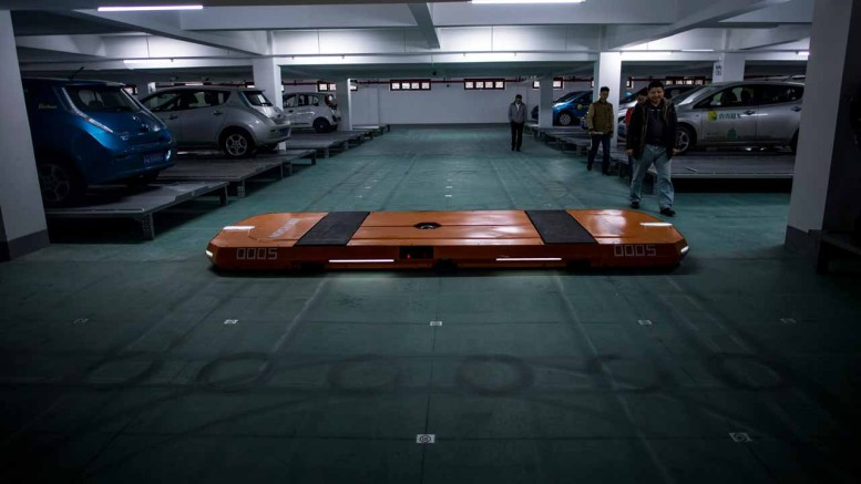 This picture taken on November 25, 2016 shows people watching a robotic unit of the smart parking system developed by Hikvision in a garage in Wuzhen Township of Tongxiang City, in east China's Zhejiang province.