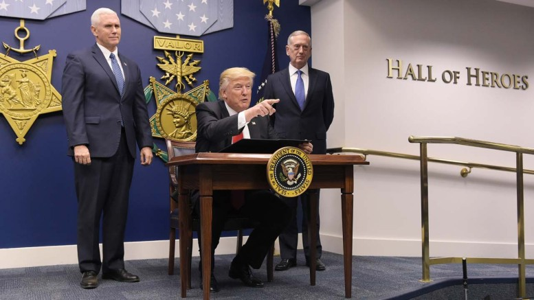 US President Donald Trump gestures before signing an executive action on rebuilding the armed forces on January 27, 2017 at the Pentagon in Washington, DC. Looking on are US Vice President Mike Pence (L) and US Defense Secretary James Mattis.