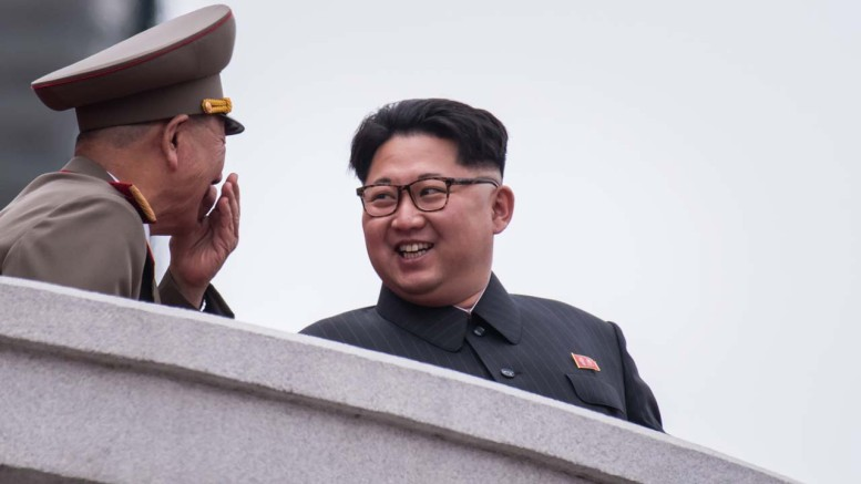 A photo taken on May 10, 2016 shows North Korean leader Kim Jong-Un (R) reacting as he talks to an unidentified soldier on a balcony of the Grand People's Study House during a military parade and mass rally on Kim Il-Sung square in Pyongyang.