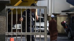 A Malaysian policeman wipes his face as he holds the gate of the forensics wing of the Hospital Kuala Lumpur where the body of Kim Jong-Nam, the half-brother of North Korean leader Kim Jong-Un, is being kept in the Malaysian capital on March 4, 2017. PHOTO: LILLIAN SUWANRUMPHA / AFP