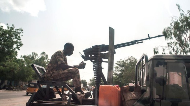 A soldier sits on the back of an armed vehicle in Maiduguri in north-east Nigeria