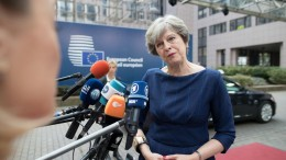Theresa May speaks to journalists as she arrives for a meeting of European Union leaders in Brussels, Belgium, on Oct. 19, 2017. Photographer: Jasper Juinen