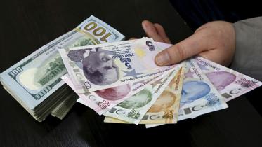 A money changer holds Turkish lira banknotes next to U