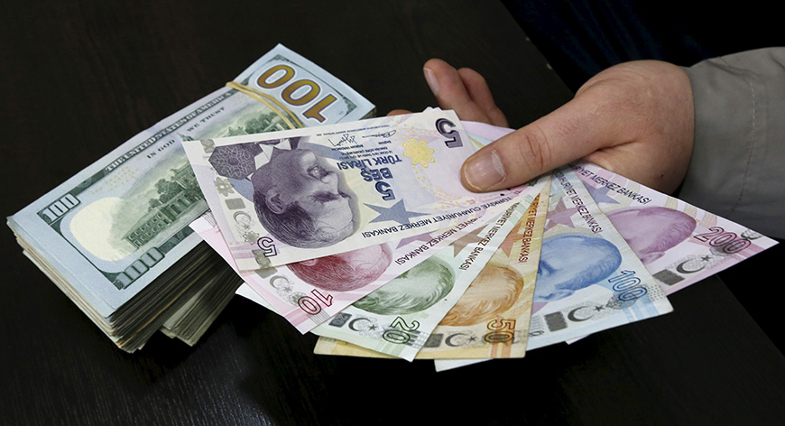 A money changer holds Turkish lira banknotes next to U