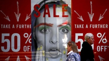 Pedestrians walk past a shop displaying advertising for a sale in central Sydney, Australia