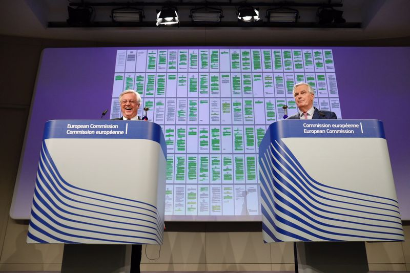 Davis and Barnier with highlighted negotiation documents projected on a screen, in Brussels on March 19.Photographer: Dario Pignatelli